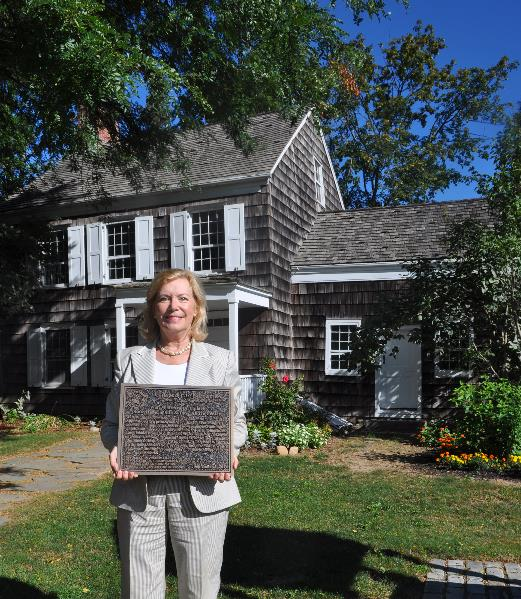 Walt Whitman Birthplace Association Executive Director Cynthia Shor stands outside the home which will be dedicated a literary landmark Sept. 5 by a division of the American Library Association.