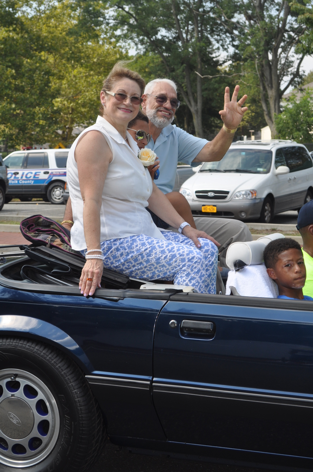 Algieri's parents, Adriana and Dominick Algieri, are all smiles atop a Mustang convertible.