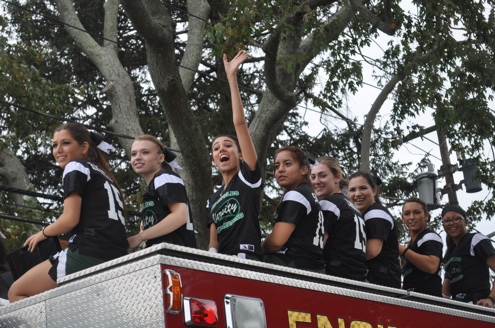 Firefighters transport the ladies of the Harborfields varsity cheerleading squad.