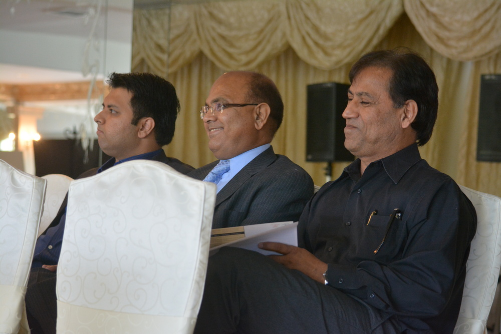 From left to right: Yama Raj, P.L. Raj and Deven Patel place their bid on the Thatched Cottage property.