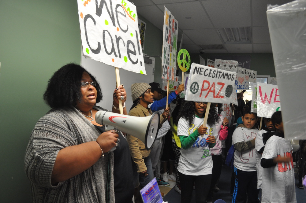 Co-organizer Crystal White speaks to supporters during a peace rally Saturday, forced indoors by rain.