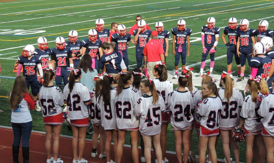 The Cold Spring Harbor football team and cheerleaders surrounded Will Schupler at the school's homecoming game.