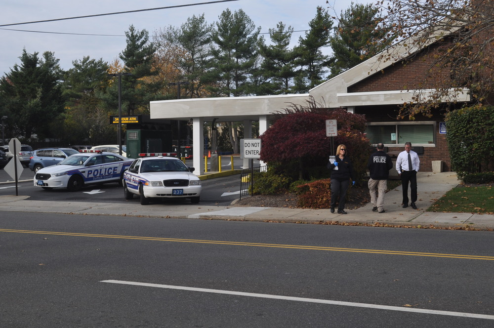 Police investigators search for evidence outside the Roslyn Savings Bank on Larkfield Road in East Northport Thursday after Nicholas Bono, of East Northport, allegedly robbed the bank at 10:30 a.m.