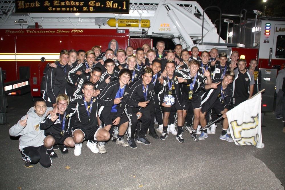 The Commack soccer team celebrates a victory in front of a Commack fire truck, which escorted them home.
