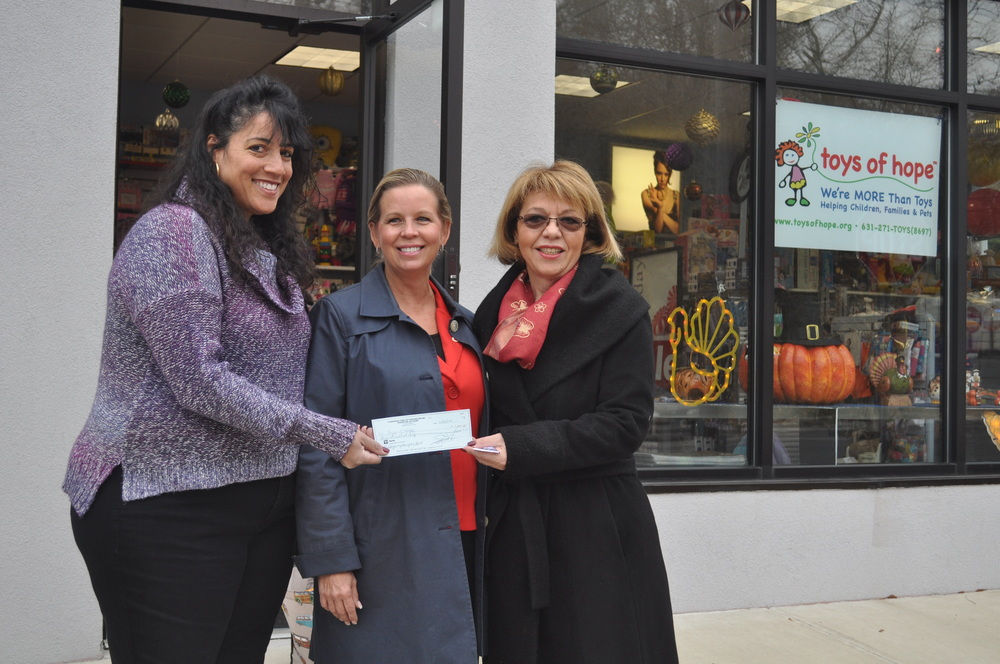 After burglars cleaned out Toys of Hope's warehouse, founder Melissa Doktofsky, left, receives a $3,000 grant from Townwide Fund of Huntington's Executive Director Trish Rongo and Grants chair Vita Scaturro Tuesday.