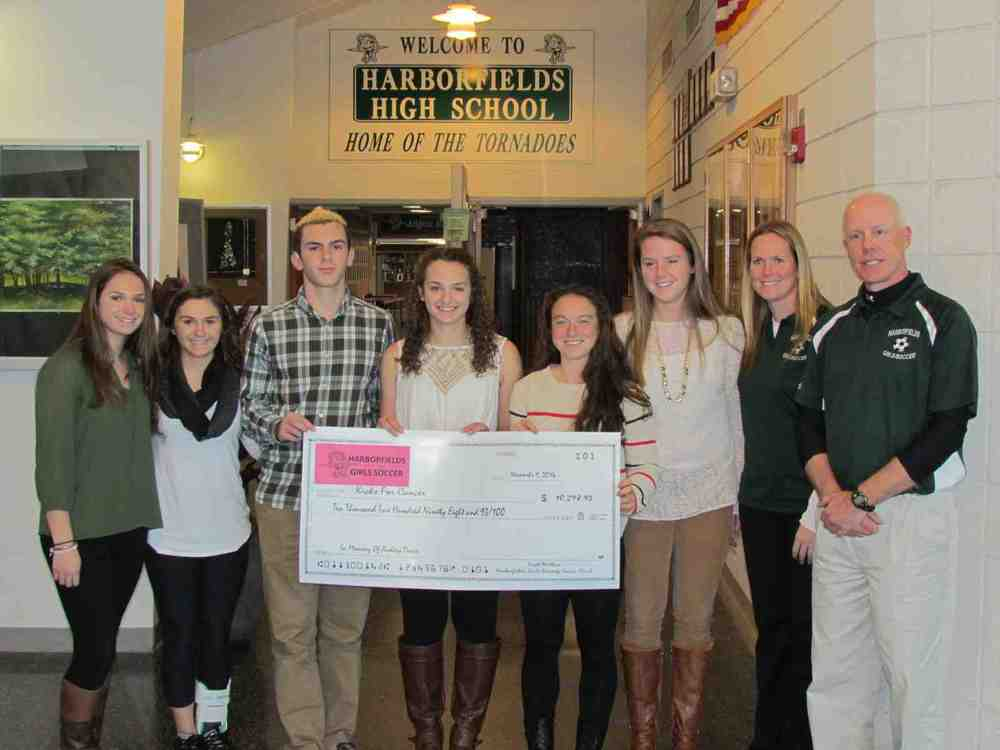 "The Davis family was presented with a check in the amount of $10,298.93 in memory of their mother, Audrey. The money was raised by the girls soccer team for the ""Kicks for Cancer"" initiative."
