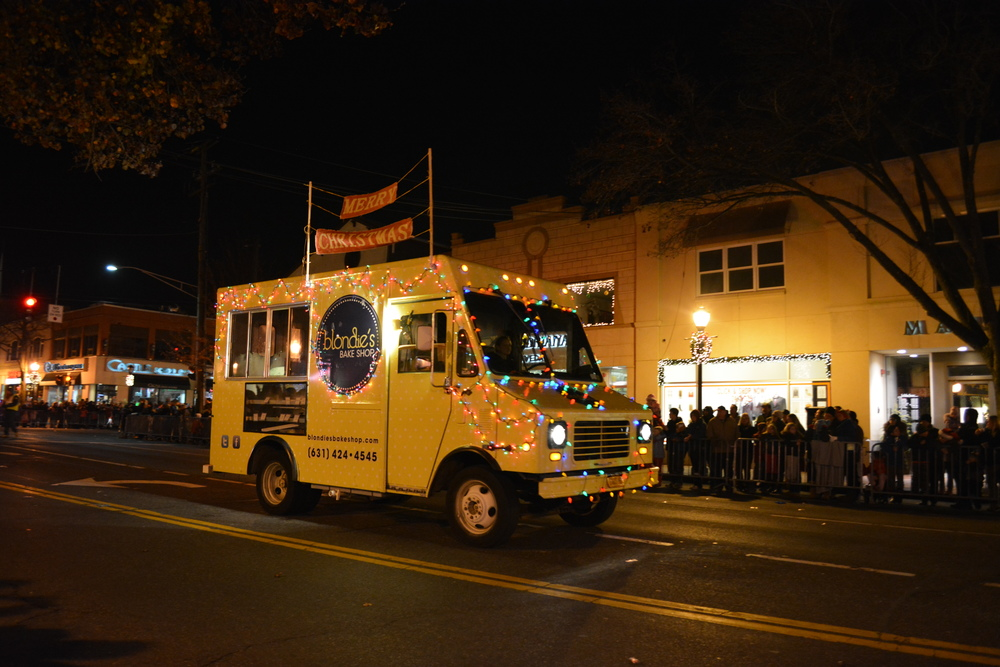 The Blondie's Bake Shop cupcake truck drives down Main Street, decked in strings of colored lights.