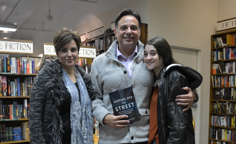 Charles Massimo smiles at his book signing with his wife, Stella, and 15-year-old daughter, Elaina.