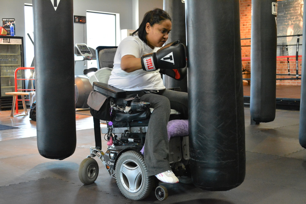 "Farzana Ali, a complete quadriplegic with limited movement in her arms, works out at Title Boxing Club in Huntington village as a part of the club's ""Power Hour"" boxing session."