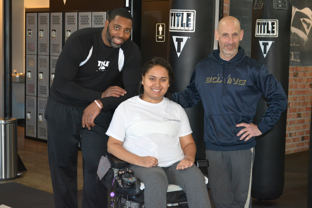 Farzana Ali, center, with one of her trainers, Ron Mason, left, and Steve Stone, Title Boxing general manager, after completing her Monday morning workout.