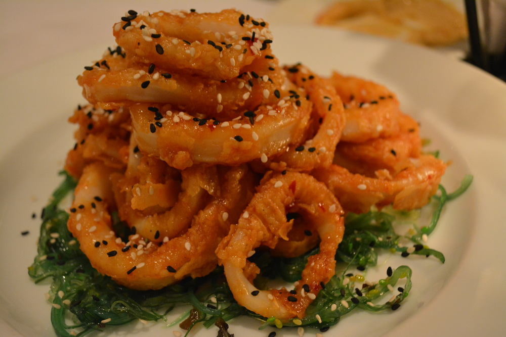 The orange-hued Thai calamari is dotted with black and white sesame seeds and served on a bed of seaweed.