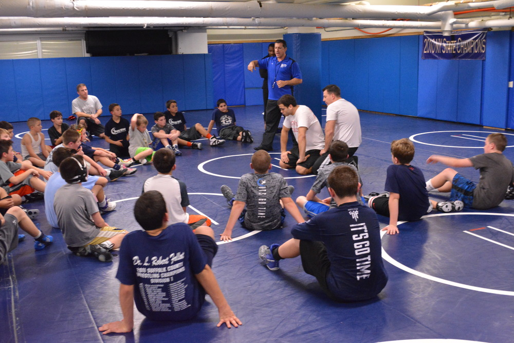 A pause in practice Dec. 8 for the Blue Wave youth wrestling program's Blue Team ends up in a teaching moment as Head Coach Thomas Giaramita (standing, center) explains what the boys will next be working on.