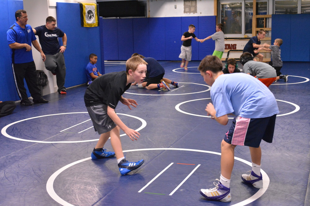 Head coach for the Blue Wave youth wrestling program, Thomas Giaramita (left) barks out orders for the organizations Blue Team during a practice at Elwood John H. Glenn High School earlier in December.