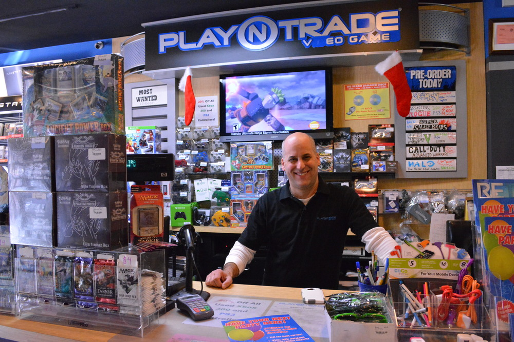 Rob Conte, owner of Huntington's Play N Trade, behind the counter at the 303 Main St. location.