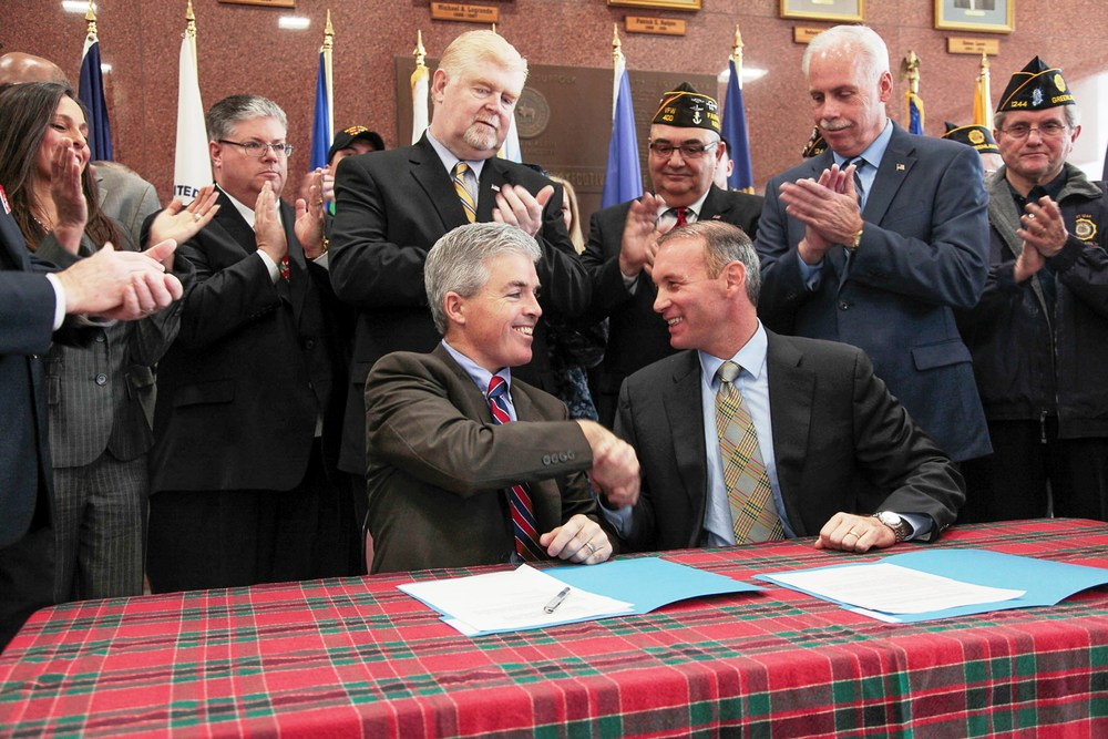 "On Dec. 22, Suffolk County Executive Steve Bellone shakes the hand of Legislator Steve Stern after signing the ""Housing Our Homeless Heroes Act"" into law."