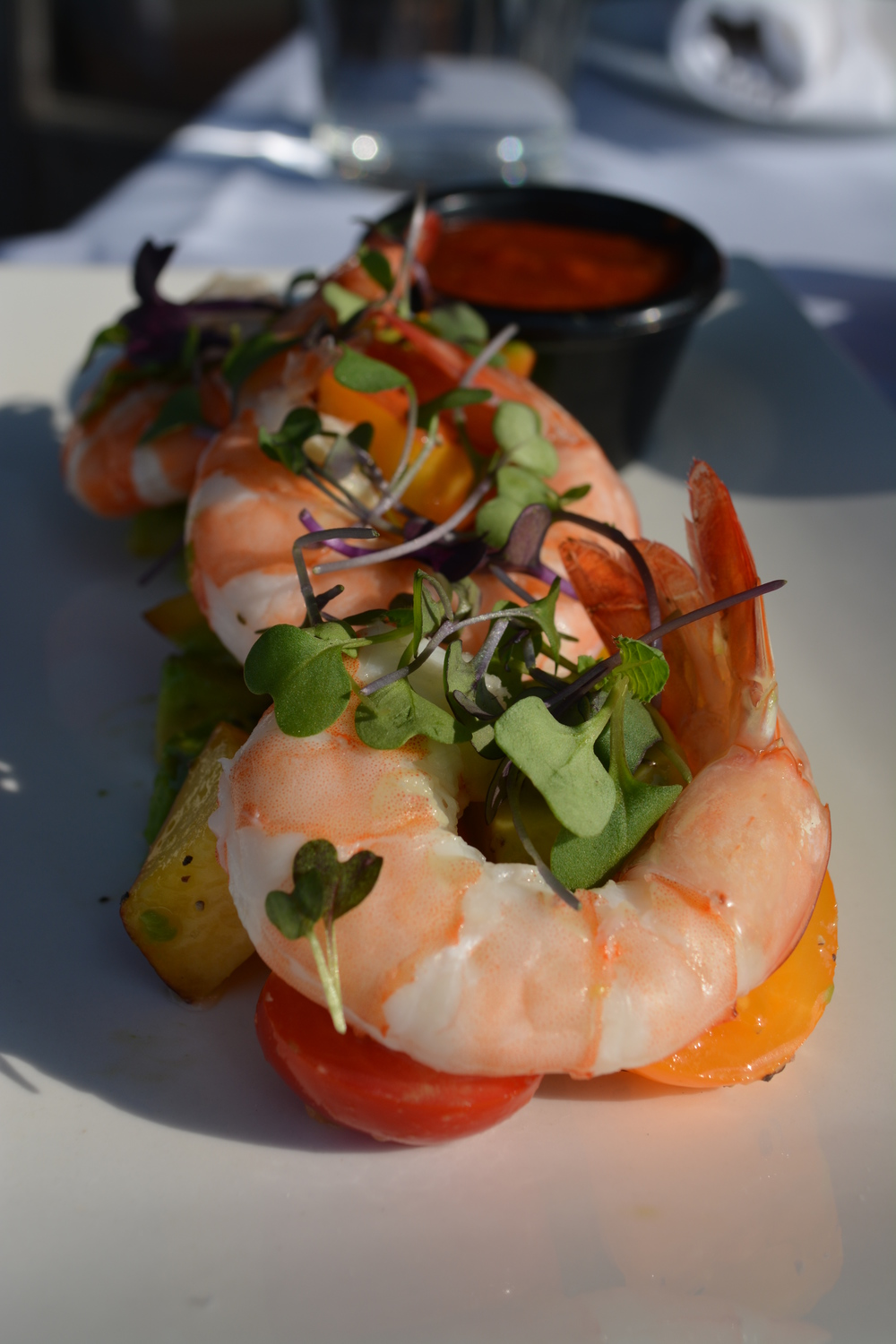 The Shrimp Cocktail appetizer ($17) features three large, pink shrimp resting on an arrangement of diced avocado, halved red and yellow cherry tomatoes and cut peaches. (Char Grille, 26 Clinton Ave., Huntington. 631-923-3400)  Long Islander News photo/ Arielle Dollinger