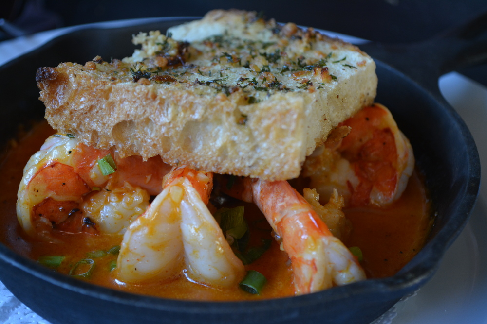 The Camarones Al Ajillo – shrimp in garlic sauce, topped with a bruchetta-like square of herb toast – is an appetizer as bold in flavor as it is in color. (Sur Argentinian Steakhouse, 314 New York Avenue, Huntington, 11743. 631-470-6300)  Long Islander News photo/ Arielle Dollinger