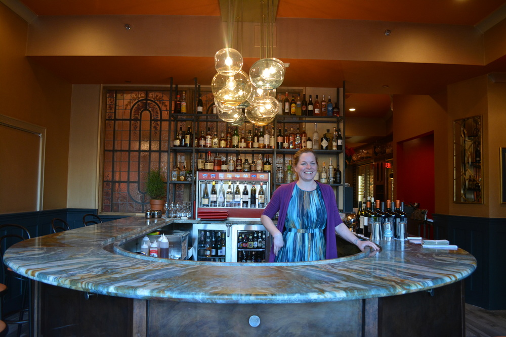 Pictured: General Manager Kelly Danek behind the bar of newly-renovated Red Restaurant.