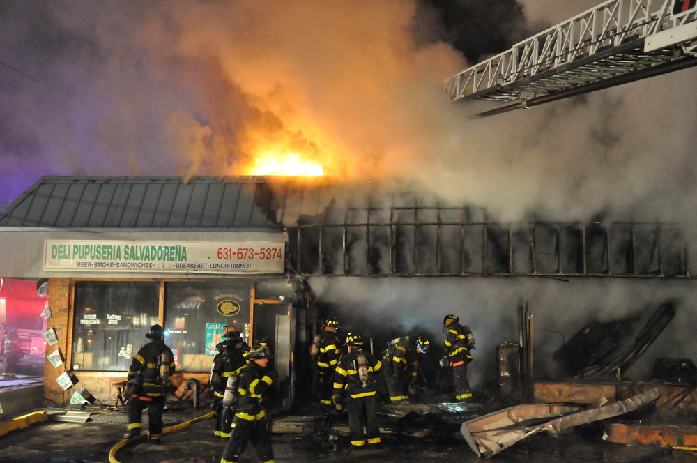 Firefighters battle a blaze in Huntington Station Wednesday morning that damaged five stores in the West Hills Shopping Center. (Photo by Steve Silverman)