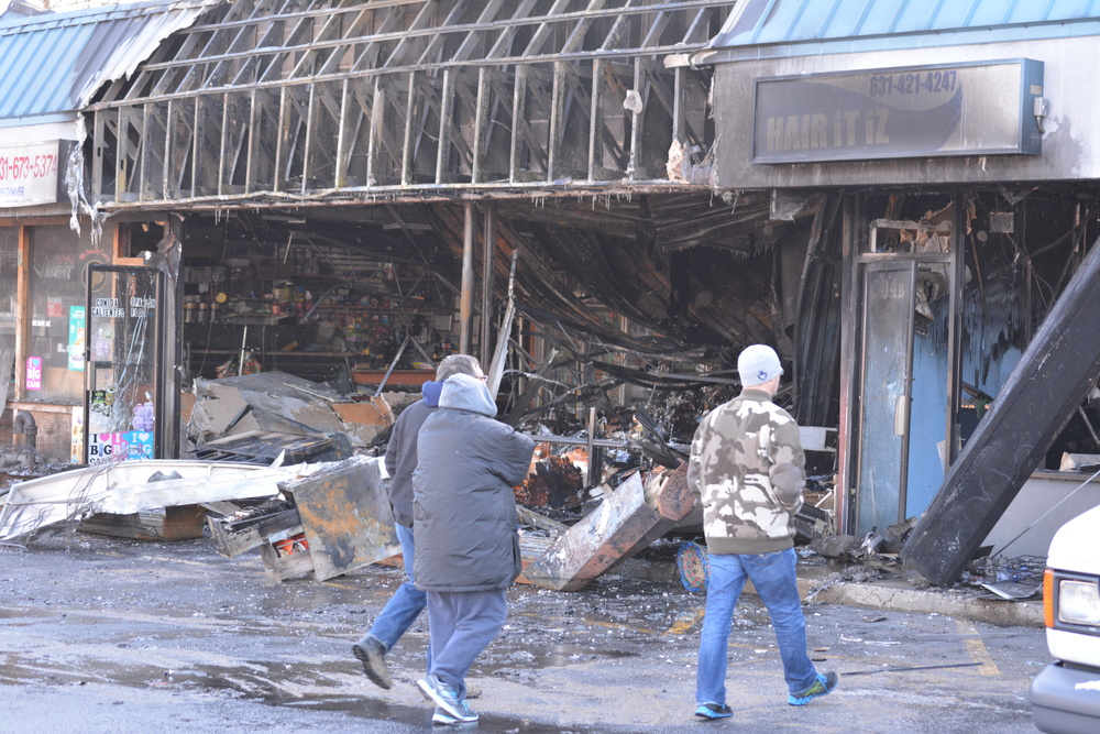 The aftermath of a Wednesday morning fire in Huntington Station, which damaged five shops in the West Hills Shopping Center on West Jericho Turnpike, is surveyed by bystanders. (Photo by Andrew Wroblewski)