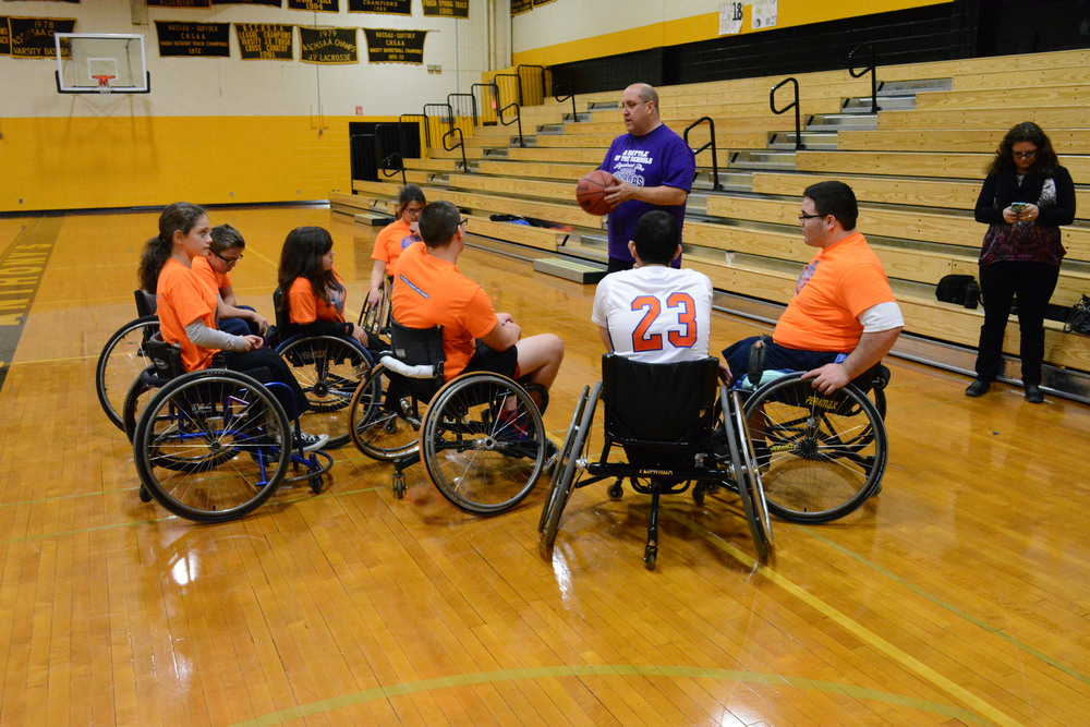 Coach Sean Clark, center, of the New York Rolling Fury youth wheelchair basketball program gives a post-practice speech to members of the team at St. Anthony's High School on Saturday,