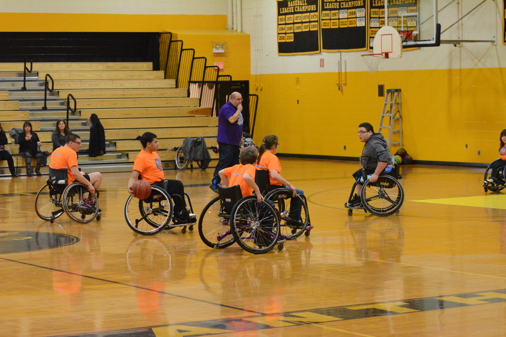 Marcos Taveras, second from left, brings the ball up court during drills on Saturday at St. Anthony's High School where the New York Rolling Fury youth wheelchair basketball team practices.
