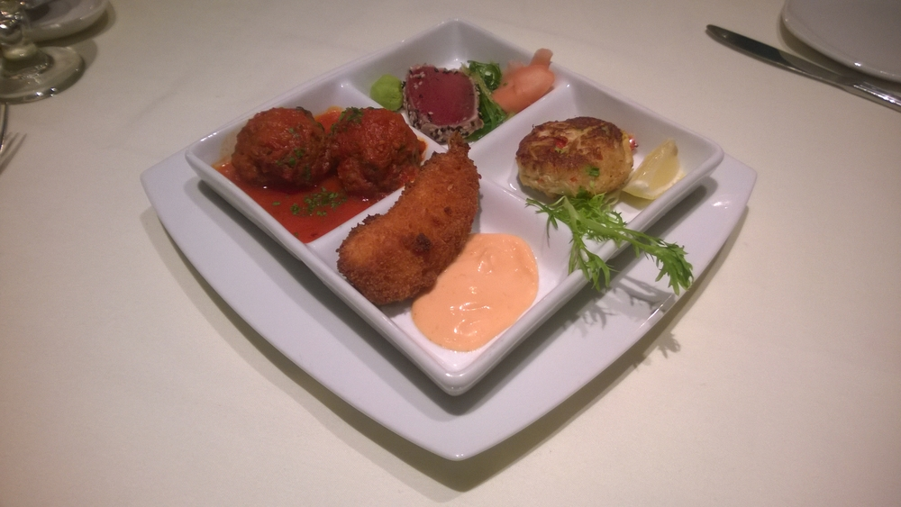 A tapas sampler: clockwise from left, meatballs, yellowfin tuna, crabcake, and provolone and bacon stuffed shrimp.