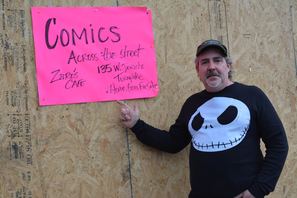 "Michael Bradley, owner of what used to be Collectors Kingdom comic shop in Huntington Station, points to a sign that directs patrons to his new, ""satellite"" comic shop, found at 135 West Jericho Turnpike."