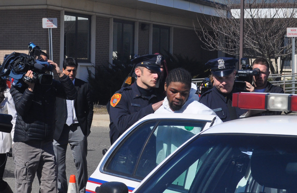 Sheldon Leftenant, 22, accused of shooting Officer Mark Collins Wednesday night, is put into a Suffolk County squad car to be transported to court in Central Islip Thursday afternoon.