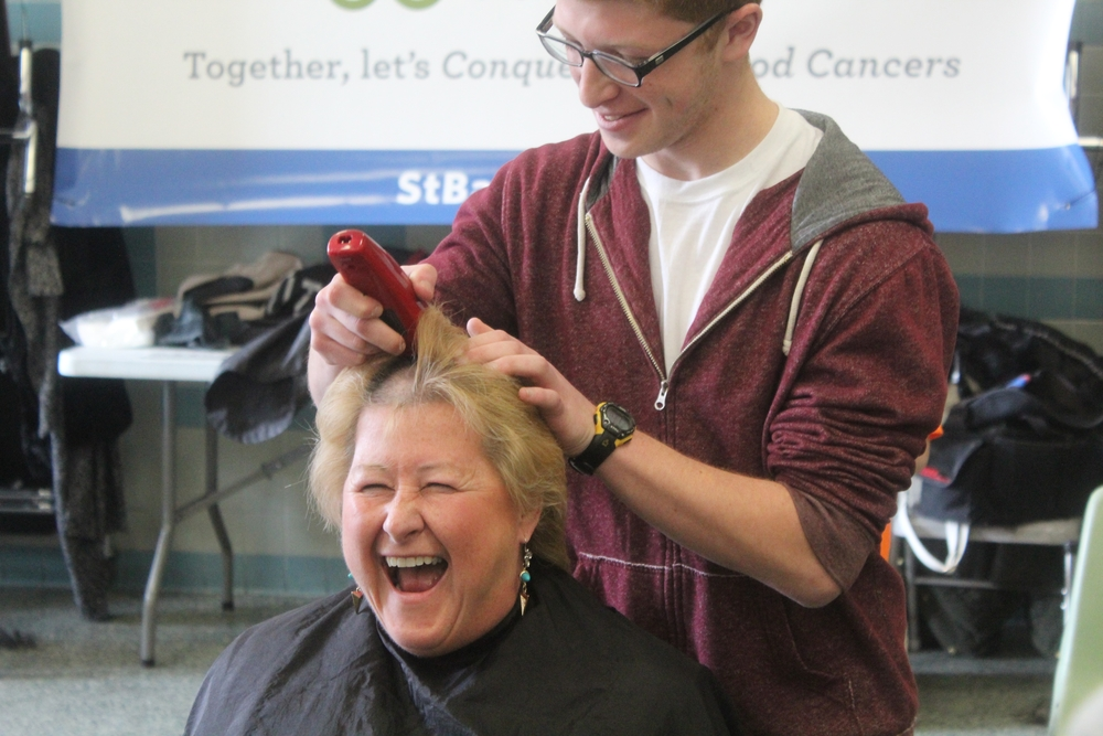 Walt Whitman High School principal Kathleen Acker goes under the razor Wednesday in support of St. Baldrick's.