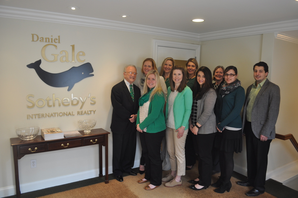 Daniel Gale Sotheby's International Realty COO Thomas Calabrese, left, and the staff at the Daniel Gale corporate offices in Cold Spring Harbor smile for a picture.