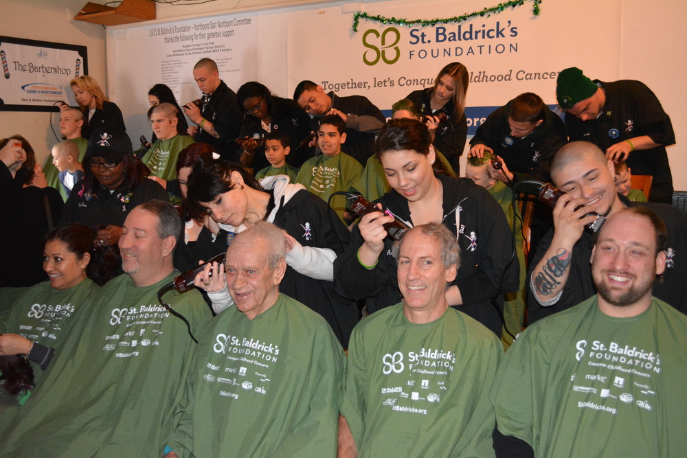 """Shavees"" – including the township-native Finnegan family – take to the chairs at Napper Tandy's Irish Pub on Saturday and the ""shavers"" – members of the Easter Suffolk BOCES Barbers – get to the shaving during the annual Northport St. Baldrick's fundraiser."