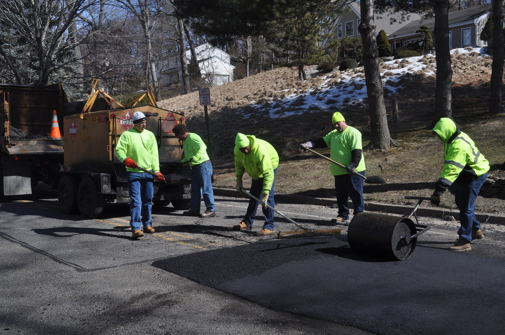 Highway workers on Monday repair a portion of Makamah Road in Fort Salonga which heaved this winter.