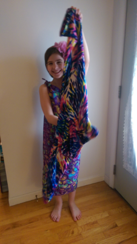 Lía Miller, wearing a dress she created, holds up a splashy printed pair of pants that she also designed.