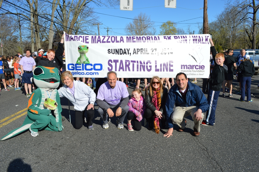 At a past Marcie Mazzola 5K are Nancy and Paul Mazzola, their grandkids Mikey, Paulie and Hailey, Huntington Councilwoman Susan Berland, State Assemblyman Chad Luppinacci and the Geico Gecko.