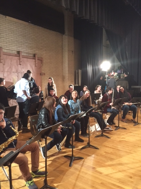 "Walt Whitman High School band members sit on the stage of Bishop Loughlin High School during a shooting for CBS's ""Elementary."" (Photo/Allan Deitz)"