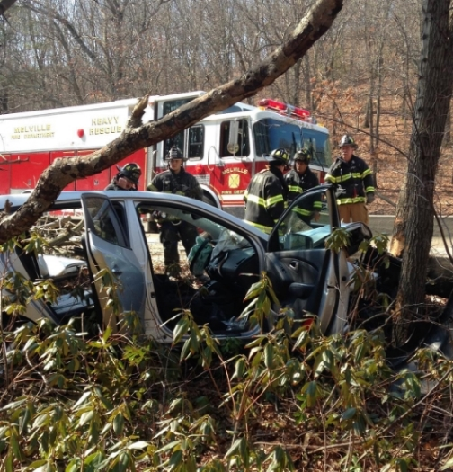 Firefighters used chainsaws to clear a path to this crashed car on the Northern State Parkway April 2. (Photo/Melville Fire Department)