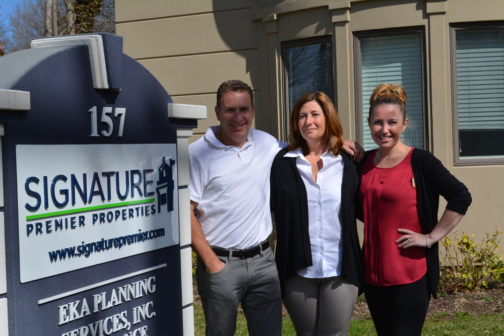 Signature Premier Properties owner and founder, Peter Morris, left, is joined for a picture outside of the realtor's Huntington office by Broker of Record Kathy Kirby-Viard, center, and Marisa Doonan.