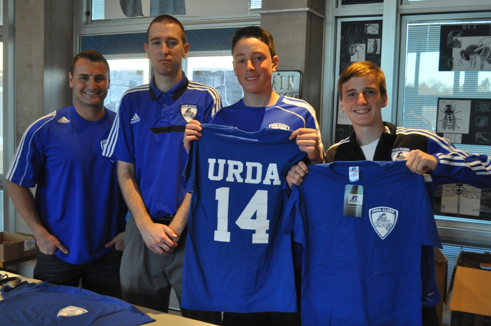 From left, junior-varsity soccer coach Joe Manaseri, Elwood Middle School coach Ken Mulvihill, freshman Chris Spalding and sophomore Andrew Lule sell t-shirts before the concert in support of the scholarship fund.