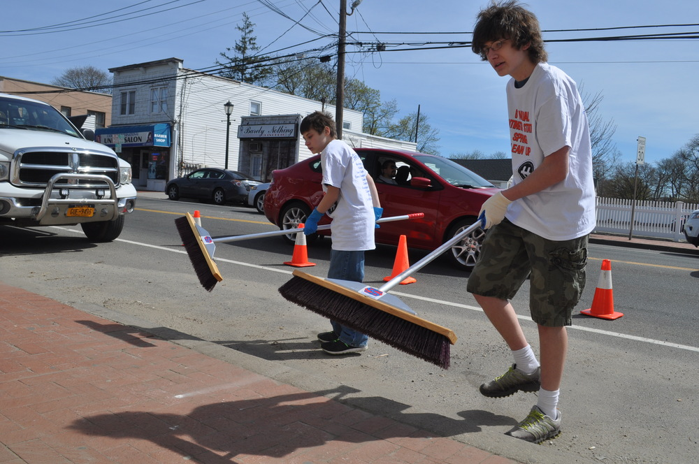 Volunteers sweep their way with brooms of all sizes to a cleaner downtown Huntington Station.
