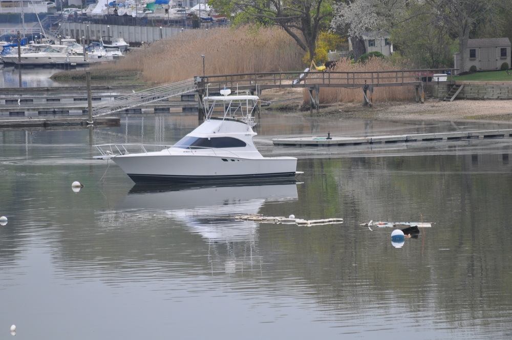 Pictured Tuesday afternoon, booms in Northport Harbor are the only visual aid to a sunken cabin cruiser, a Centerport resident said, and he wants the town to mark the wreck until it's removed.