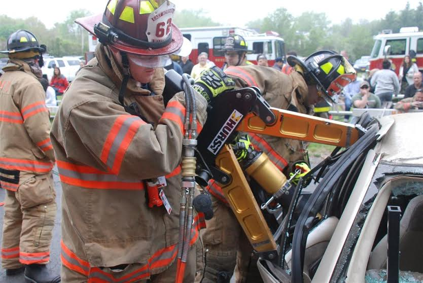 An East Northport competitor goes to work, applying the Jaws of Life to a mangled car.