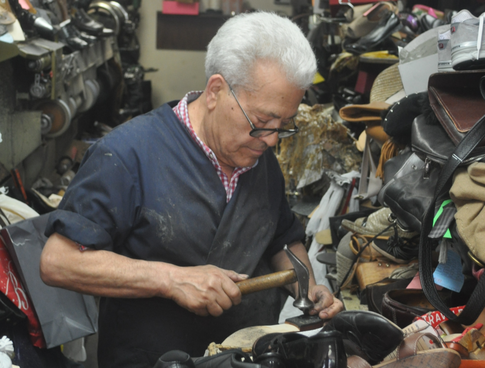 Andrea Sorrentino works his craft at his shoe repair shop in Huntington.