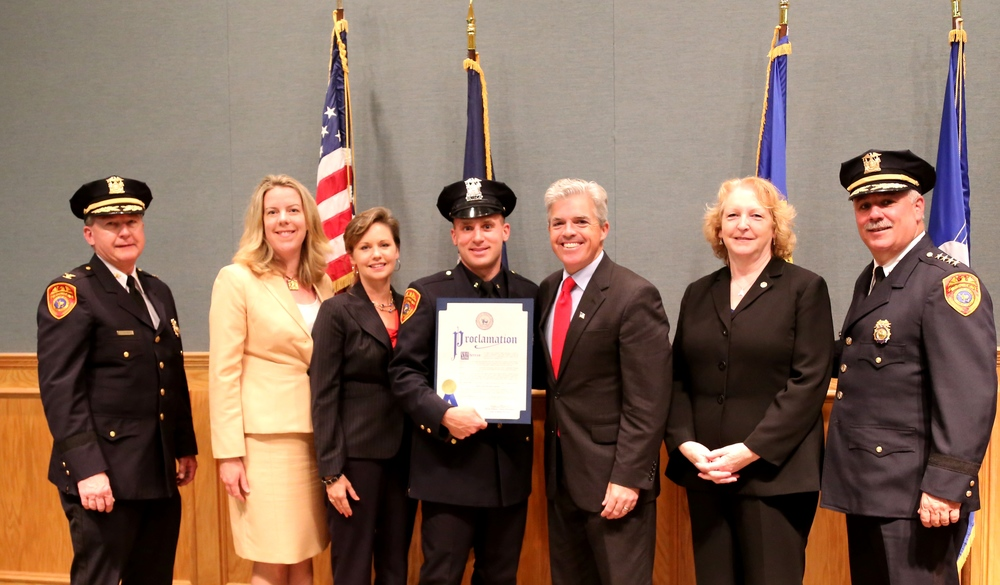 Officer Josh Parsons, holding the proclamation, pictured with local officials.