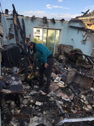 Caitlyn Shea combs through the remains of her townhouse after a devastating fire destroyed her Melville home at The Villages West complex.