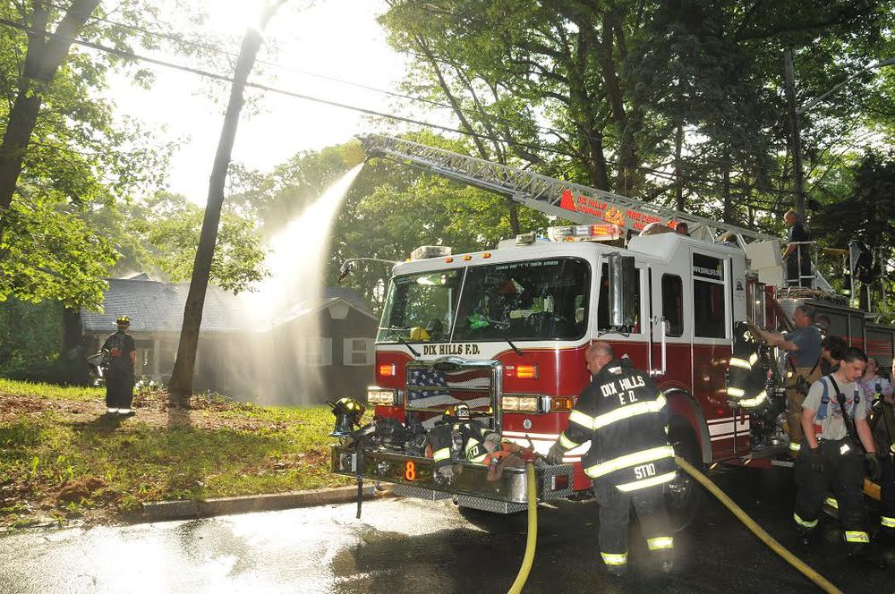 A fire truck douses the home, which town officials said is expected to be the subject of a blight hearing on Tuesday, June 2. (Photo by Steve Silverman)