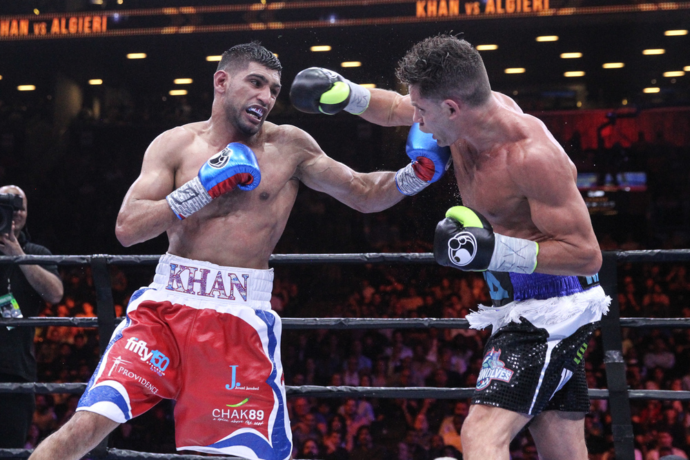 Greenlawn native Chris Algieri, right, throws a right hook at English boxer Amir Khan on Friday night at the Barclays Center in Brooklyn.