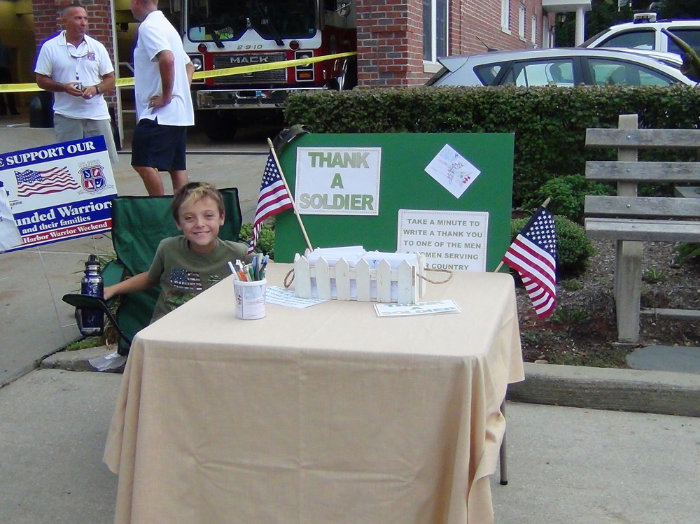 Twelve-year-old William Connor, of Northport, runs his Thank A Soldier table at a Northport Wounded Warrior parade; Connor founded Thank A Soldier to create and gather thank-you postcards to mail out to United States servicemen and servicewomen.