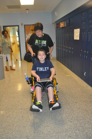 Eli Mollineaux and his aide, Ilene Messina in the halls of Finley Middle School June 12.
