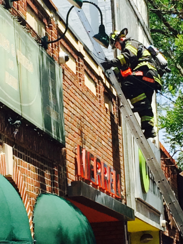 Pictured, a Huntington Fire Department volunteer climbs to the roof of Renarts shoe store at 289 Main St. in Huntington to search for the source of a potential fire.